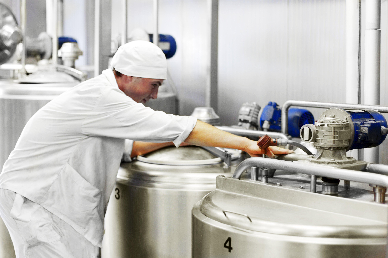 Worker at dairy. milk tanks